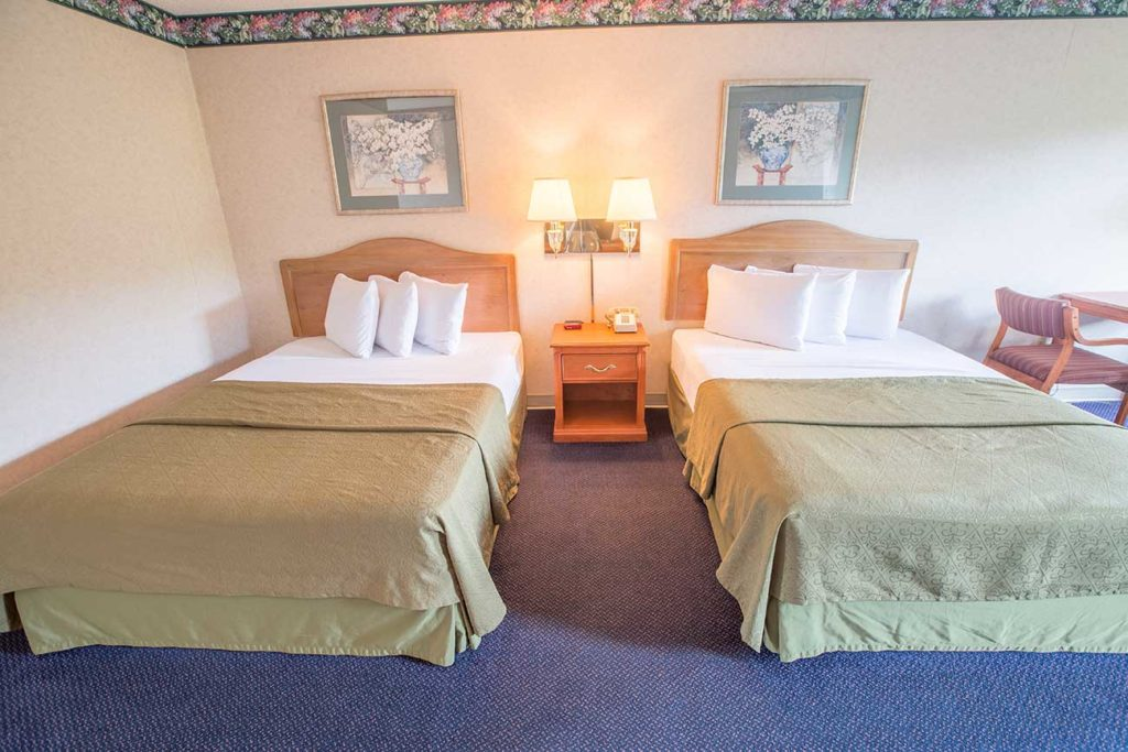 2 beds with green comforters in hotel room